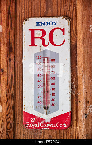 Vintage or antique Royal Crown Cola (RC Cola) thermometer advertising the soda drink on an old cabin wall in rural Alabama. - Stock Image