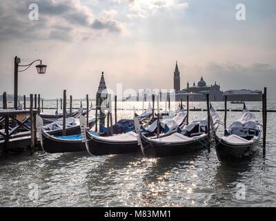 Italy, in winter: snow on gondolas in St Mark's Square, Venice, with the island of San Giorgio Maggiore in the - Stock Image
