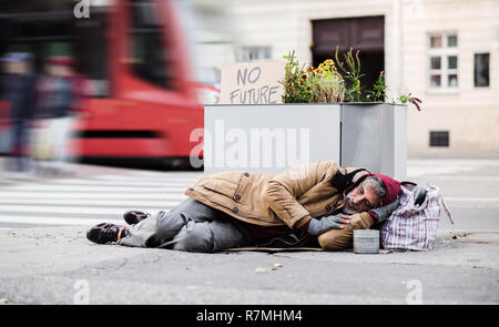 A homeless beggar man lying on the ground outdoors in city asking for money donation. - Stock Image