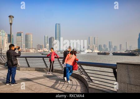 29 November 2018: Shanghai, China - Visitors on The Bund, beside the Huangpu River, Shanghai. - Stock Image