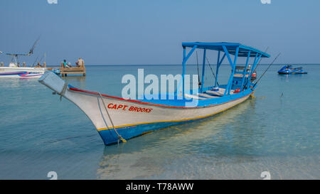 Traditional wooden boat used as a tourist fishing boat in Wesy Bay Roatan Honduras. - Stock Image