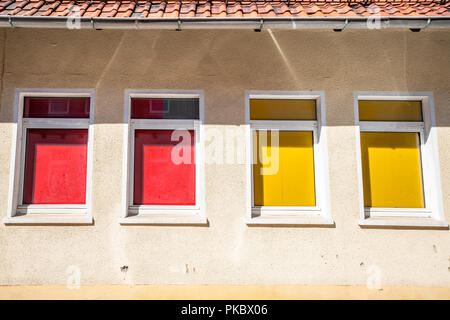 Four colorful windows on a building with red and yellow curtains - Stock Image