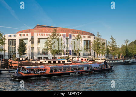 Tourist sightseeing boat travelling by the National Opera and Ballet theatre, Amstel 3, 1011 PN Amsterdam, Netherlands. - Stock Image