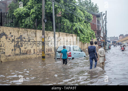 Youth walking in a flooded street after the rains in New Delhi, India. - Stock Image