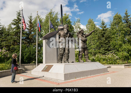 A tourist views the Lend Lease Monument in downtown riverfront park in Fairbanks, Alaska. The statue depicts Russian and American WWII pilots, commemorating Alaska as the staging ground in the Lend-Lease program which provided nearly 8,000 aircraft to the eastern front. - Stock Image