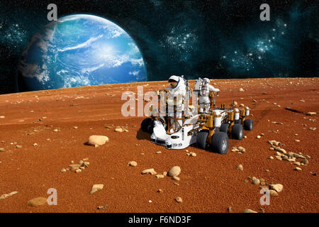 A team of astronauts explore a barren moon on a rover. The moon's water-covered parent planet rises over the - Stock Image