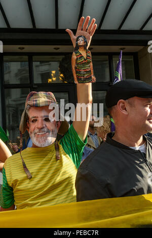 London, UK. 13th August 2018.  A protester in a Lual mask holds up an arm with a picture of Dilma as Brazilians protest outside the Brazilian embassy calling for the release of Luiz Inacio Lula da Silva, a former trade union leader who was President of Brazil from 2003-11 to enable him to stand for election again in October. Credit: Peter Marshall/Alamy Live News - Stock Image