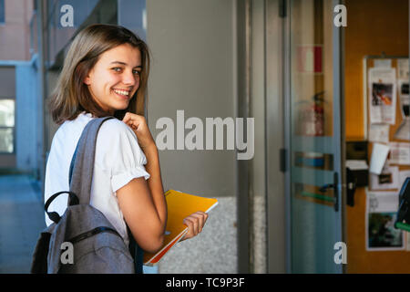 Portrait of a smiling student girl at school entrance - Stock Image