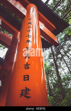 An isncription on one of the 10,000+ toti gates at the Fushimi Inari Shrine  in Kyoto, Japan - Stock Image