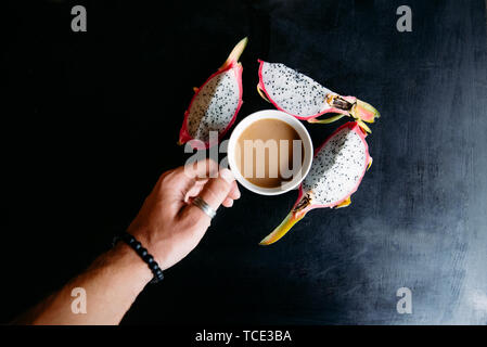 Man's hand holding a cup of tea and wedges of dragon fruit - Stock Image