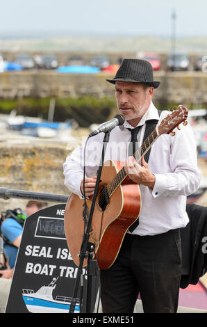 A busker playing the guitar on The Wharf, St Ives, Cornwall, England, U.K. - Stock Image