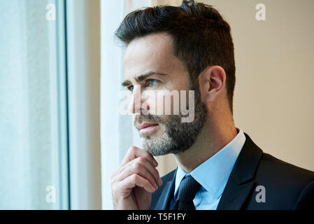 Businessman looking through office window - Stock Image