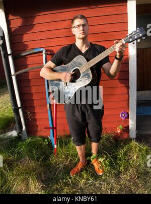 Man playing guitar in the sun, Northern Sweden. - Stock Image