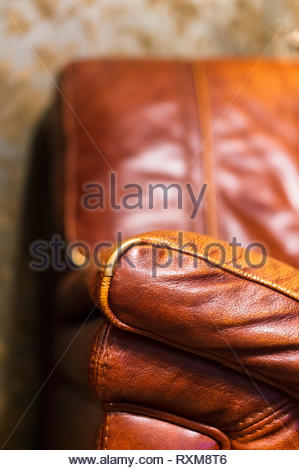 Close up of a brown leather seat in soft focus background. - Stock Image