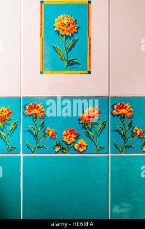 Old blue, orange and white wall times from the 1970s with painted flowers. - Stock Image