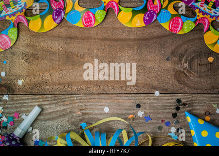 Mardi Gras background with carnival masks, streamer and confetti on wooden table with copy space - Stock Image