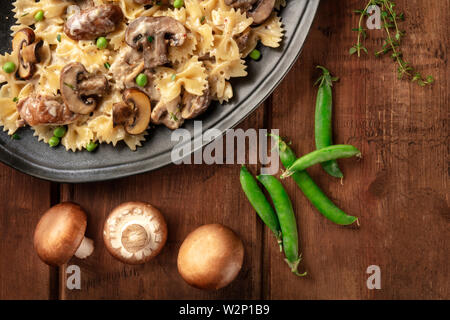 Mushroom and cheese pasta. Farfalle with cremini and green peas close-up - Stock Image