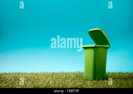 Green recycle bin on green grass and blue sky - Stock Image