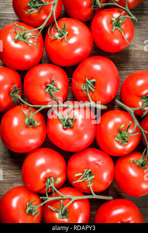 Fresh ripe tomatoes . On a wooden table. - Stock Image