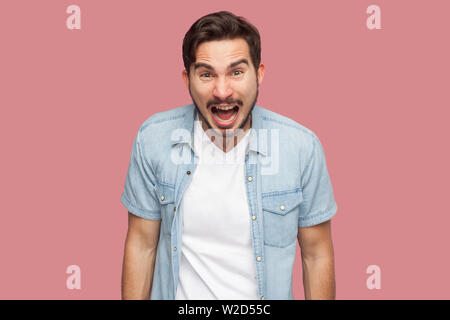 Portrait of aggressive shocked handsome bearded young man in blue casual style shirt standing looking and screaming at camera with angry face. indoor - Stock Image