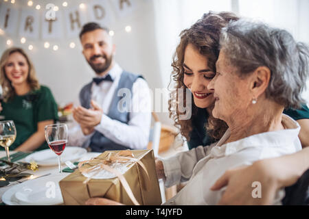 An elderly grandmother celebrating birthday with family and receiving a gift box, a party concept. - Stock Image