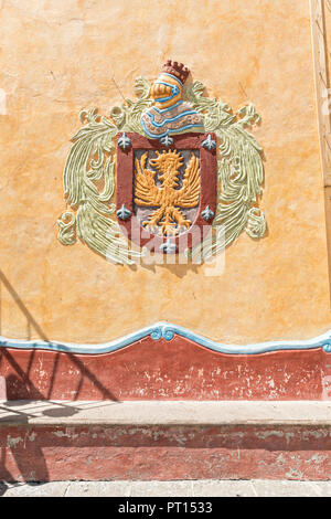 The city coat of armor displayed above a stone bench in the Plaza Principal in the beautiful colonial village of Bernal, Queretaro, Mexico. Bernal is a quaint colonial town known for the Pena de Bernal, a giant monolith which dominates the tiny village is the third highest on the planet. - Stock Image
