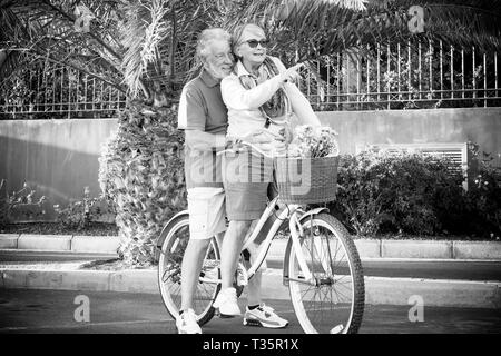 Black and white picture couple man and woman senior mature people enjoying and have fun riding both the same old vintage bike together - forever toget - Stock Image
