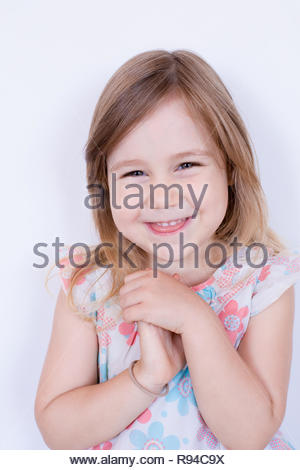 portrait of three years old blonde girl, with white dress with red and blue flowers  looking, smiling with tender expression, standing isolated in whi - Stock Image