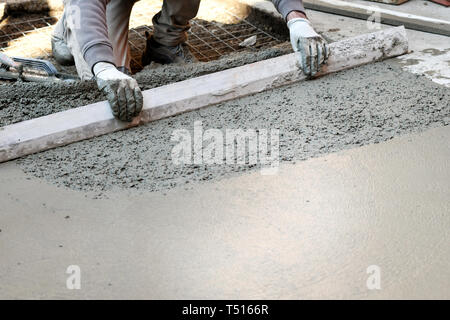 Worker spreading and flattening cement mortar with hand tool, making concrete floor - Stock Image