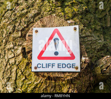 Sign on a tree warning of a cliff edge ahead - Stock Image
