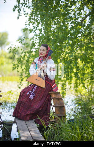 Young smiling woman in traditional russian clothes sits on the small bridge near the lake, and holding balalaika - vertical shot - Stock Image