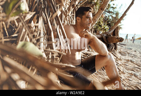 Portrait of a handsome, muscular man relaxing on a tropical beach - Stock Image
