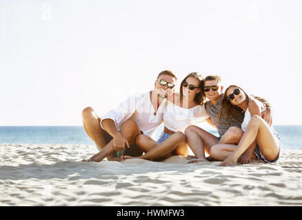 Group four friends fun on a beach - Stock Image