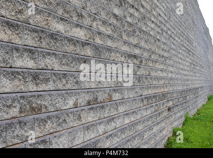 A concrete wall, built of  blocks creating horizontal rows, with a radiused setback for each row,. - Stock Image