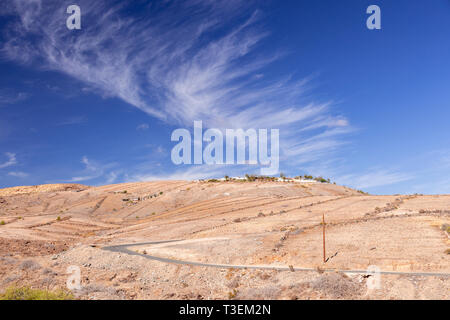 Road through dry landscape at Meloneras, Gran Canaria, Canary Islands with cirrus clouds overhead - Stock Image