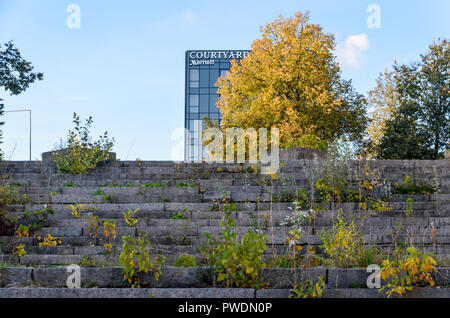 Grass growing on the staircase of the disused Vilnius Palace of Concerts and Sports, with fancy hotel in the background - Stock Image