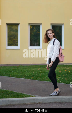 Portrait of a first-year student girl with a backpack on background of academic building. Concept of teaching pre-entry courses, students - Stock Image