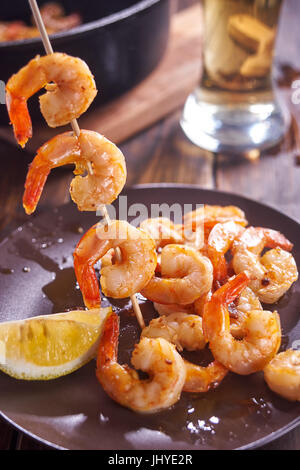 Shrimps on stick for barbecue. - Stock Image