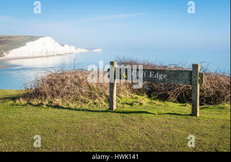 Sign warning of cliff edge at Seaford Head Nature Reserve, East Sussex, with the Seven Sisters cliffs in the background - Stock Image