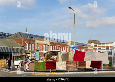 Outdoor stall selling rugs and carpets on Bolton market. The indoor market is in the background building. - Stock Image
