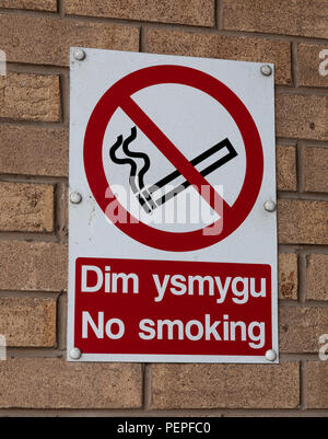 Bilingual no smoking sign in English and Welsh on an exterior brick wall Wrexham Wales June 2018 - Stock Image