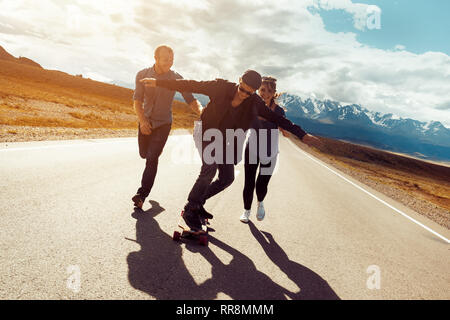 Happy friends are havin fun and skating or longboarding at long straight road - Stock Image