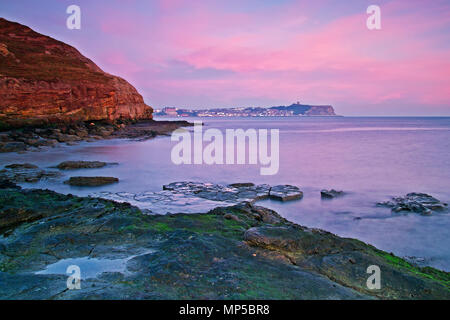 Dawn breaking over Scarborough Castle headland and an incoming tide, with views northwards over the North Sea from a rock pool in Cornelian Bay. - Stock Image