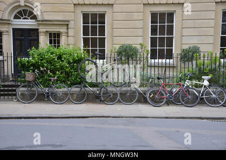 Bicycles chained to railings including a novel way of storage one above the other, Oxford - Stock Image