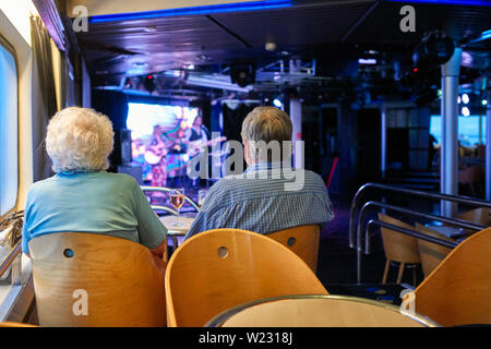 An older couple viewed from behind enjoying the entertainment in the bar of a ferry travelling to Brittany - Stock Image