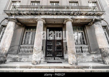 Greek pillar building with weathered windows and facade - Stock Image