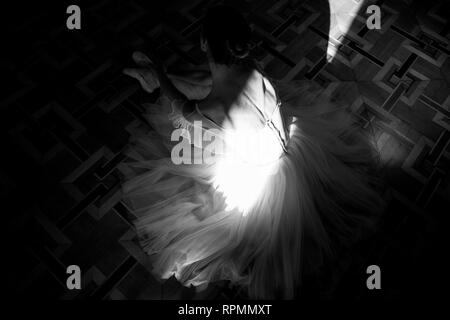 Beautiful ballerina sitting on the floor and lit by a sunbeam. Black and white image. Top view. - Stock Image