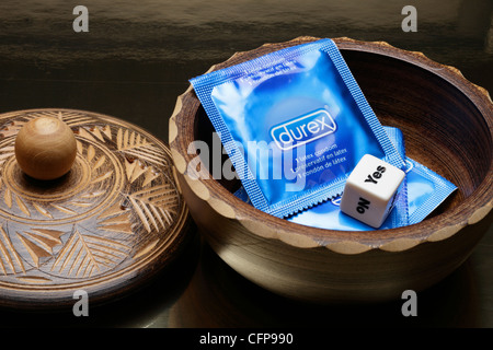 Condoms in wooden bowl with yes/no die - Stock Image