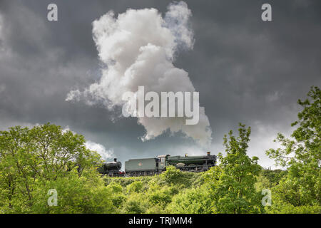Side view of vintage UK steam train passing through English countryside puffing out steam on GWSR heritage line, sunny afternoon but dark clouds above. - Stock Image