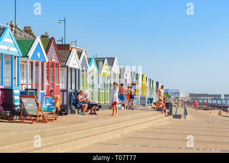 Southwold, UK - September 11, 2018 - People enjoying the sunshine on the promenade of Southwold beach lined with a row of beach huts - Stock Image